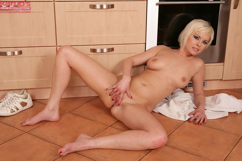 Соблазнительная блондинка Laura Sweet раздевается на кухне и играет пальчиками в свое вагине