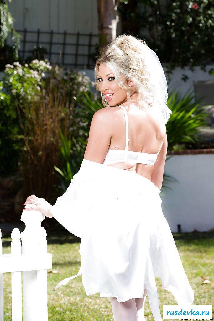 Красивая голая невеста в свадебном платье у забора | Фото