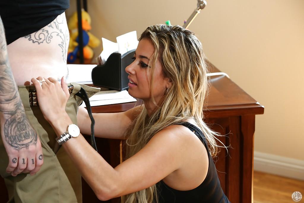 Сексуальная мамаша стоя на коленях отсасывает татуированному партнёру
