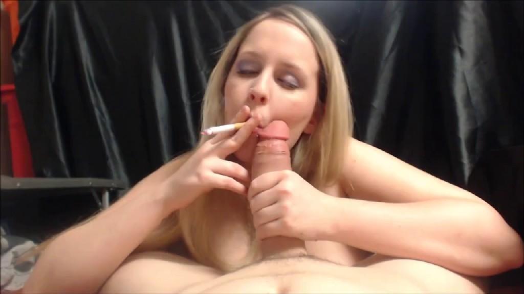 Блондинка курит сигарету и сосет член своему дружку по яйца