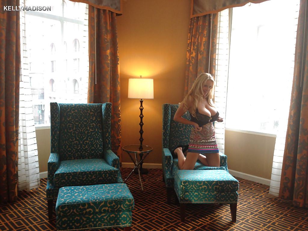 Грудастая блондинка раздевается в кресле гостиной