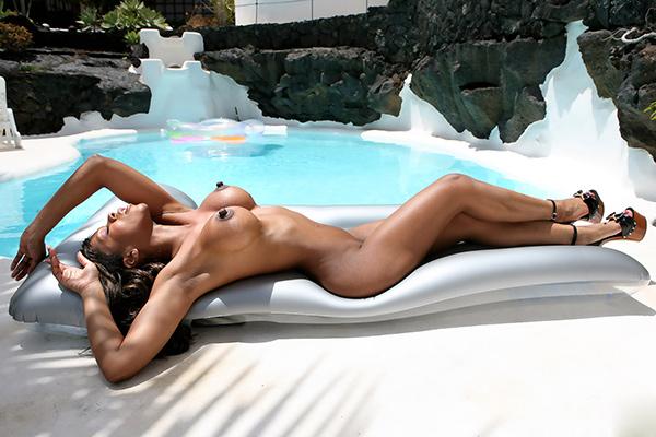 Молодая мулатка позирует у бассейна
