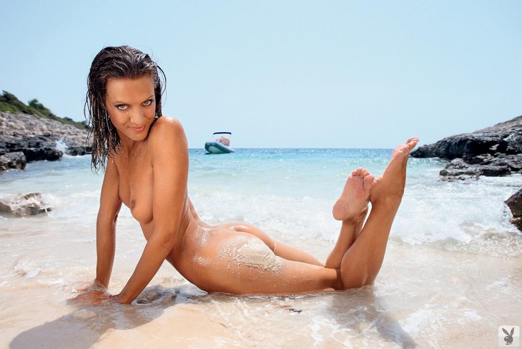 Сексуальная брюнетка позирует голой показывая свое стройное тело на берегу моря