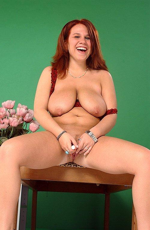 Рыжая пухлая дама смеется поглаживая вагину вибратором