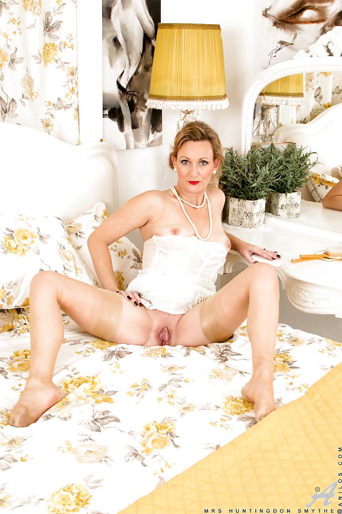 Накрашенная мамка в белом белье позирует и демонстрирует дырку в цветочной комнате