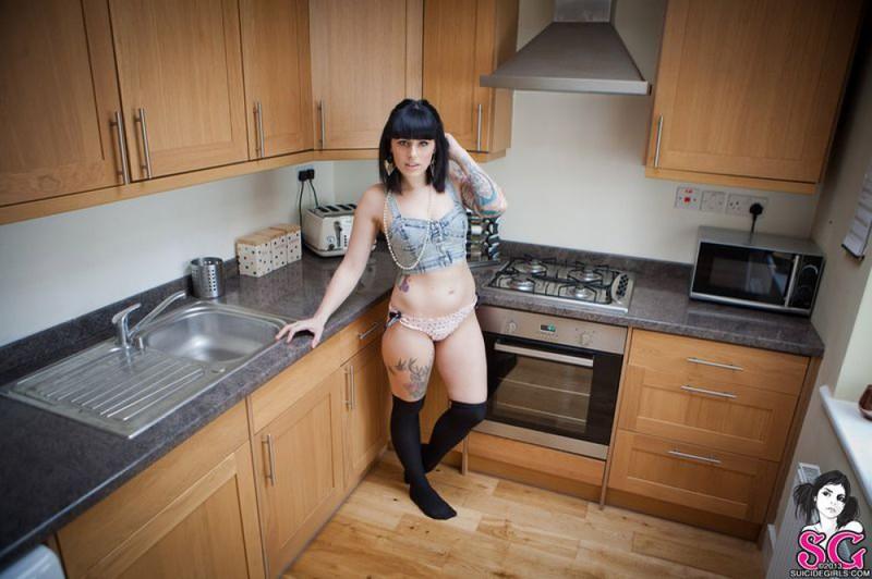 Татуированная молодая неформалка в чулках позирует голая на кухне