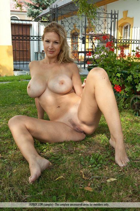 Симпатичная блонда Karol стоит раком на траве и старается посильнее раздвинуть ноги для показа волосатой пизды