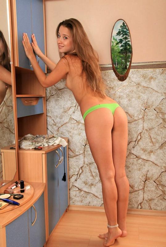 Восемнадцатилетняя девушка позирует в своей комнате возле зеркала